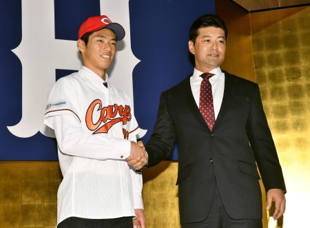 広島の新入団記者会見で、緒方監督(右)と握手をするドラフト1位の中村奨成捕手=13日、広島市