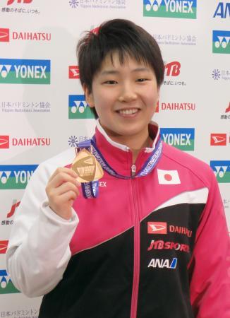 バドミントンのSSファイナルの金メダルを掲げる女子シングルスの山口茜=18日、成田空港