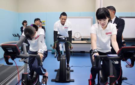 低酸素室でバイクをこぐ(右から)卓球の平野美宇、陸上のサニブラウン・ハキームら若手有望選手=26日、東京都北区の国立スポーツ科学センター