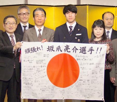 東京都内で行われた壮行会で、寄せ書き入りの日の丸を手にするショートトラック男子日本代表の坂爪亮介(中央右)=25日午後