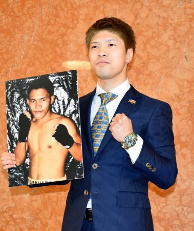 対戦相手となるロニー・バルドナドの写真を手にポーズをとる田中恒成=30日、名古屋市