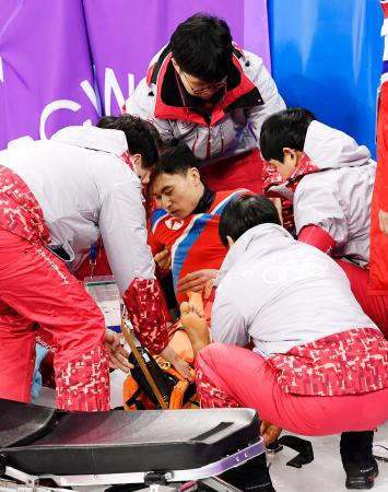 本番リンクでの公式練習で激しく転倒し、担架に乗せられるショートトラック男子の北朝鮮のチェ・ウンソン選手(中央)=江陵(共同)