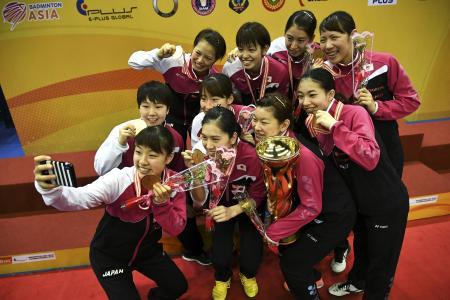 バドミントンのアジア団体選手権で優勝し、金メダルやトロフィーを手に自撮りする奥原希望(左端)ら日本の選手たち=11日、アロースター(ゲッティ=共同)
