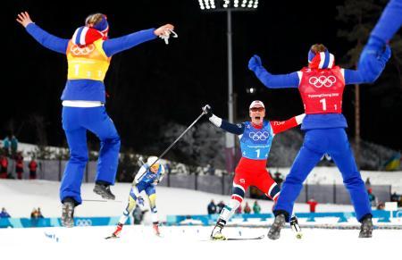 スキー距離女子20キロリレー、トップでゴールするノルウェーのアンカー、マリット・ビョルゲンを歓喜で出迎えるチームメートたち=17日、平昌(AP=共同)
