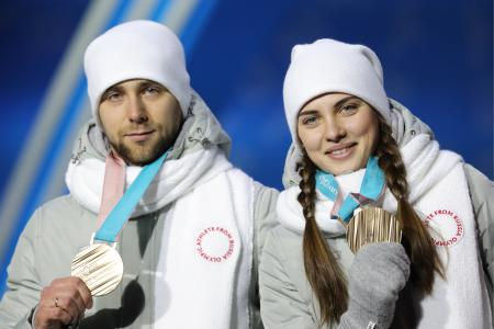 カーリング混合ダブルスで3位となり、銅メダルを手にする男子のアレクサンドル・クルシェルニツキー選手(左)=14日、平昌(タス=共同)