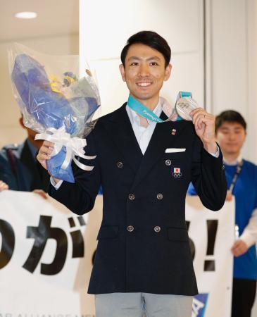 平昌冬季五輪から帰国し、銀メダルを手に笑顔を見せる渡部暁斗選手=24日午後、羽田空港