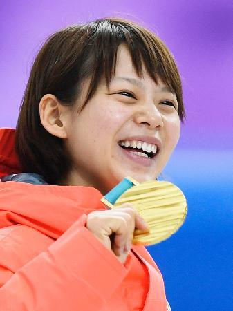平昌冬季五輪のスピードスケート女子マススタートで獲得した金メダルを手に笑顔の高木菜那=24日、韓国・江陵(共同)