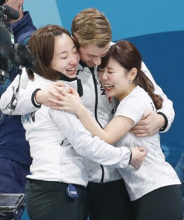 カーリング女子で銅メダルを獲得し、リンドコーチ(中央)と抱き合って喜ぶ藤沢(左)と吉田夕=江陵(共同)