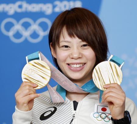 スピードスケート女子の団体追い抜きとマススタートで獲得した二つの金メダルを手に笑顔の高木菜那選手=25日、韓国・平昌(共同)