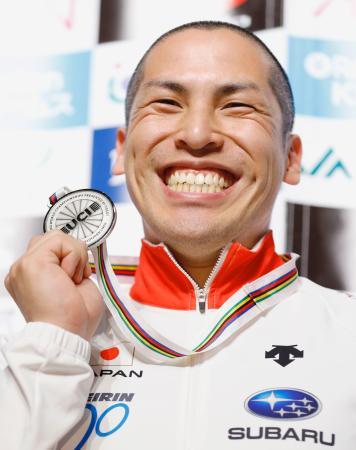 世界選手権男子ケイリンで獲得した銀メダルを手に笑顔の河端朋之=6日、羽田空港