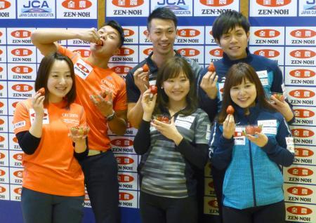 カーリングの日本混合ダブルス選手権を前に、提供されたイチゴを手にポーズをとる選手たち。前列左から藤沢、吉田知、吉田夕、後列左から山口、清水、両角友=13日、青森市