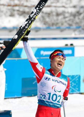 スキー距離男子10キロクラシカル立位でゴール後、スタンドに向かってスキーを掲げる新田佳浩。金メダルを獲得した=平昌(共同)
