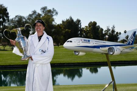 全日空機の模型の横でトロフィーを掲げるリンドベリ=2日、ランチョミラージュ(USA TODAY・ロイター=共同)