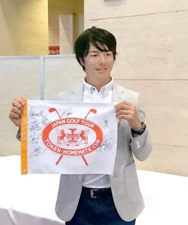 サイン入りピンフラッグを手にする石川遼=10日、三重県桑名市