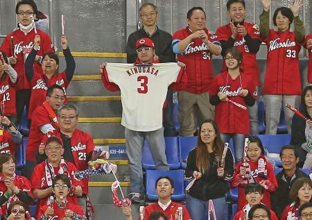 DeNA戦で衣笠祥雄氏のユニホームを掲げる広島ファン(中央)=24日夜、横浜スタジアム