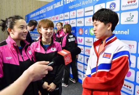 韓国との統一チームで準決勝に臨むことになり、取材を受ける北朝鮮のキム・ソンイ(右)=3日、スウェーデン・ハルムスタード(共同)