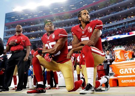 試合前に流れる国歌を片膝をついて聴くフォーティナイナーズの選手たち=2016年9月、サンタクララ(AP=共同)