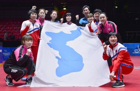 卓球世界選手権団体戦を終え、統一旗を囲みポーズをとる女子の南北合同チーム「コリア」=5月、スウェーデンのハルムスタード