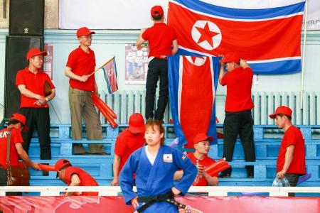 柔道の東アジア選手権で北朝鮮チームが敗退し、国旗を片付ける応援団=10日、ウランバートル(共同)