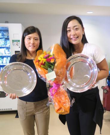 テニスの全仏オープン女子ダブルスで獲得した準優勝のプレートを手に笑顔を見せる穂積(右)と二宮=12日、羽田空港