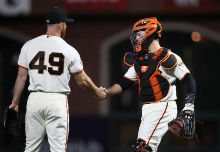 6月19日のマーリンズ戦で試合後に投手と握手を交わすジャイアンツのポージー(右)=サンフランシスコ