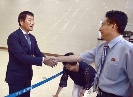 平壌国際空港で元吉友体育次官(右)に見送られる国際体操連盟の渡辺守成会長=14日(共同)