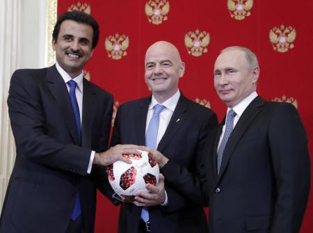 サッカーボールと写真に納まる(左から)次回W杯開催国カタールのタミム首長、FIFAのインファンティノ会長、ロシアのプーチン大統領=15日、モスクワ(タス=共同)