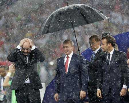 15日、モスクワのルジニキ競技場で行われた決勝戦後、頭に手をやるインファンティノFIFA会長(左)と傘の下に立つロシアのプーチン大統領(中央)、それを見るフランスのマクロン大統領(右)(AP=共同)