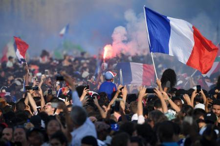 16日、W杯ロシア大会で優勝したフランス代表が凱旋パレードしたパリで国旗を振るサポーターたち(ロイター=共同)