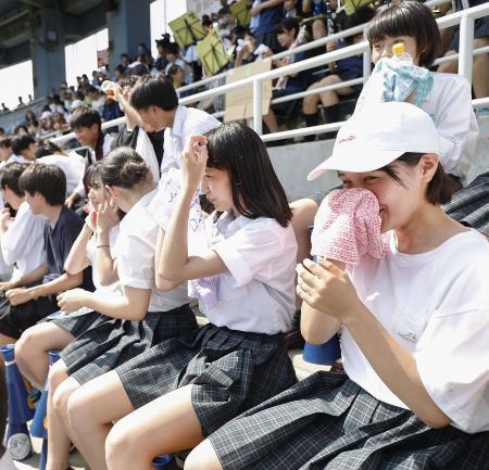全国高校野球選手権東東京大会の会場で、汗をぬぐいながら応援する高校生=19日、東京都江戸川区