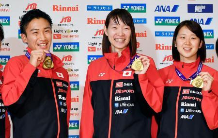 バドミントンの世界選手権で獲得した金メダルを手に、笑顔を見せる(左から)男子シングルスの桃田賢斗、女子ダブルスの松本麻佑、永原和可那の各選手=6日午後、羽田空港