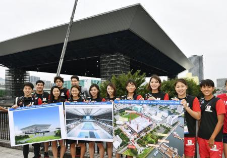 建設が進む「五輪水泳センター」を視察し、完成予想図のパネルを手にする瀬戸大也(左端)ら競泳の日本代表=7日午後、東京都江東区