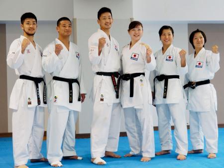 記者会見後にポーズをとる荒賀龍太郎(中央左)、植草歩(同右)らアジア大会の空手の組手代表=11日、東京都江東区