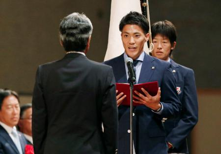 ジャカルタ・アジア大会の日本選手団結団式で、決意表明する主将で陸上男子の山県亮太選手。奥は旗手でソフトボール女子の上野由岐子選手=13日午後、東京都内のホテル