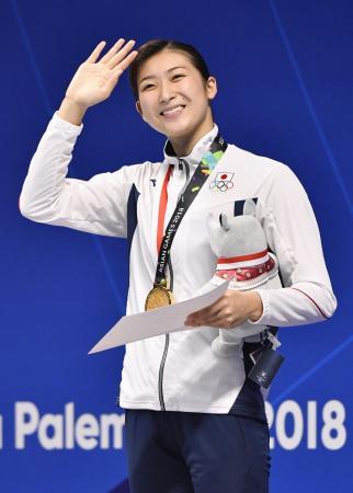 ジャカルタ・アジア大会の競泳女子100メートルバタフライで優勝し、表彰台で笑顔の池江璃花子。大会四つ目の金メダルを獲得した=21日、ジャカルタ(共同)