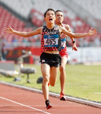 男子マラソン バーレーン選手(奥)と競り合いながら1位でゴールする井上大仁=ジャカルタ(共同)