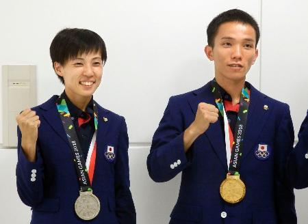 ジャカルタ・アジア大会から帰国した、マラソンで男子金メダルの井上大仁(右)と女子銀メダルの野上恵子=27日、成田空港