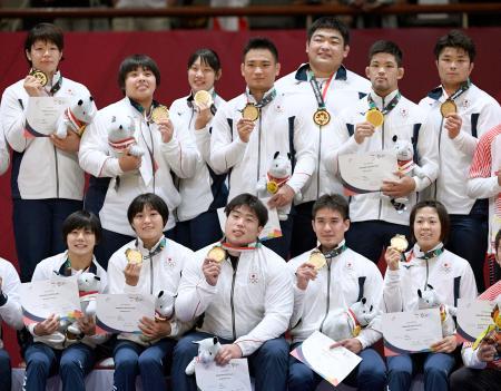 混合団体で優勝し金メダルを手に笑顔の日本チーム=ジャカルタ(共同)