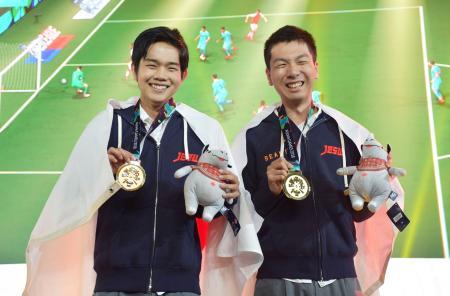 ジャカルタ・アジア大会の公開競技「eスポーツ」の人気サッカーゲーム「ウイニングイレブン」で優勝し、笑顔で金メダルを手にする杉村直紀選手(右)と相原翼選手=1日、ジャカルタ(共同)