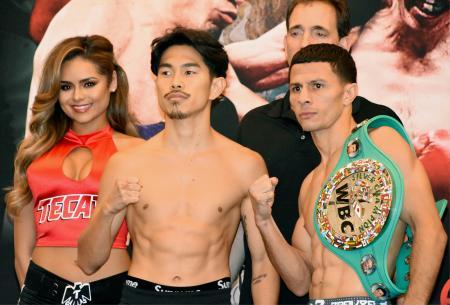 前日計量を終え、対戦相手とポーズをとる井岡一翔(中央)。右は対戦相手のマクウィリアムズ・アローヨ=7日、ロサンゼルス(共同)