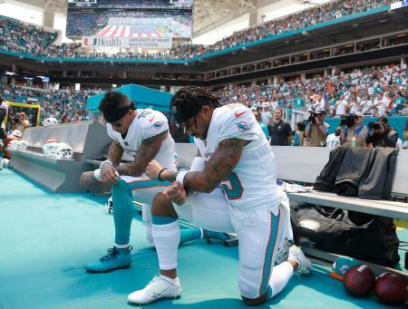 NFLタイタンズ戦での国歌斉唱で、膝をついて人種差別に抗議の意を表すドルフィンズのWRスティルズ(左)とWRウィルソン=9日マイアミガーデンズ(AP=共同)
