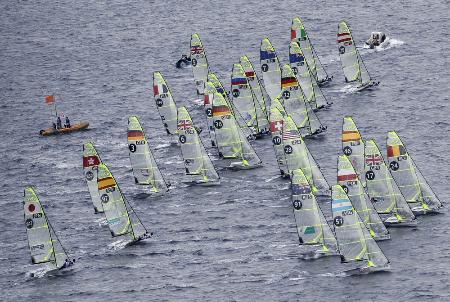 セーリングのW杯江の島大会で一斉にスタートする選手たち=11日、神奈川県藤沢市の江の島沖