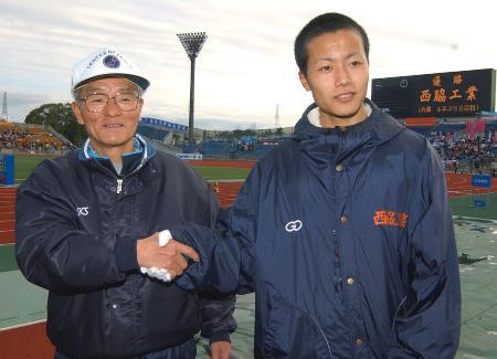 2002年の全国高校駅伝で通算8度目の優勝を飾り、最終走者の阿江匠(右)と握手する西脇工の渡辺公二監督(当時)=西京極陸上競技場
