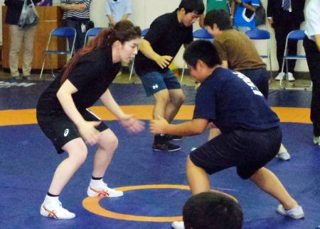 レスリング競技の体験会で、子どものタックルを受ける吉田沙保里選手(左)=22日午前、千葉県松戸市の市立相模台小