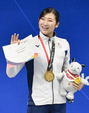 ジャカルタ・アジア大会の女子50メートル自由形で優勝し、表彰台で手を振る池江璃花子。6冠を達成した=ジャカルタ(共同)