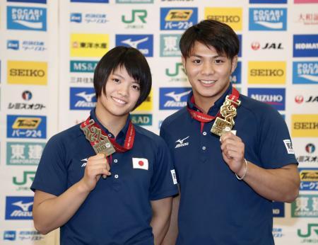 記者会見を終え、メダルを手に写真に納まる男子66キロ級優勝の阿部一二三(右)と女子52キロ級優勝の妹、阿部詩=29日夜、成田空港