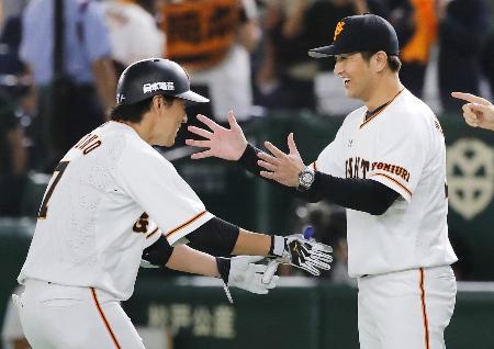サヨナラ打を放った長野(左)を笑顔で迎える巨人・高橋監督=東京ドーム