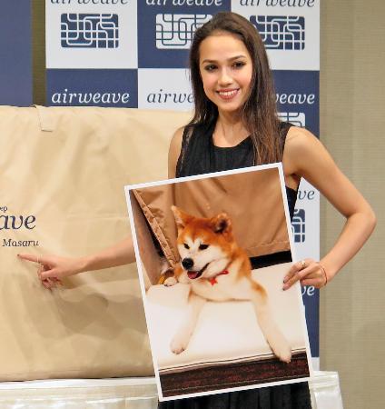 愛犬マサルの写真を手に笑顔のアリーナ・ザギトワ=4日、さいたま市