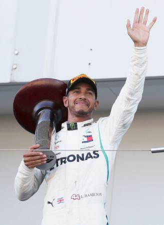 F1日本グランプリで優勝し、表彰台で声援に応えるメルセデスのルイス・ハミルトン=鈴鹿サーキット