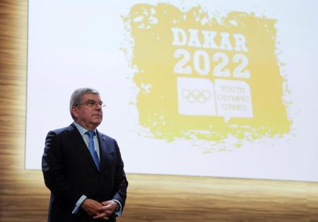 2022年ダカール夏季ユース五輪のロゴと国際オリンピック委員会(IOC)のバッハ会長=8日、ブエノスアイレス(ロイター=共同)